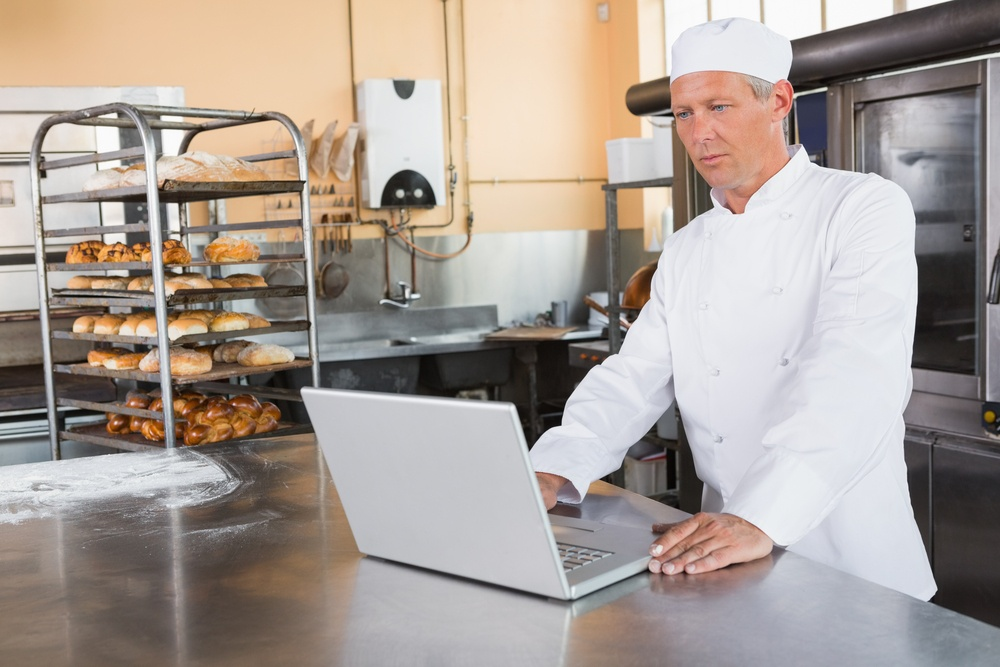 Focused baker using laptop on worktop in the kitchen of the bakery.jpeg